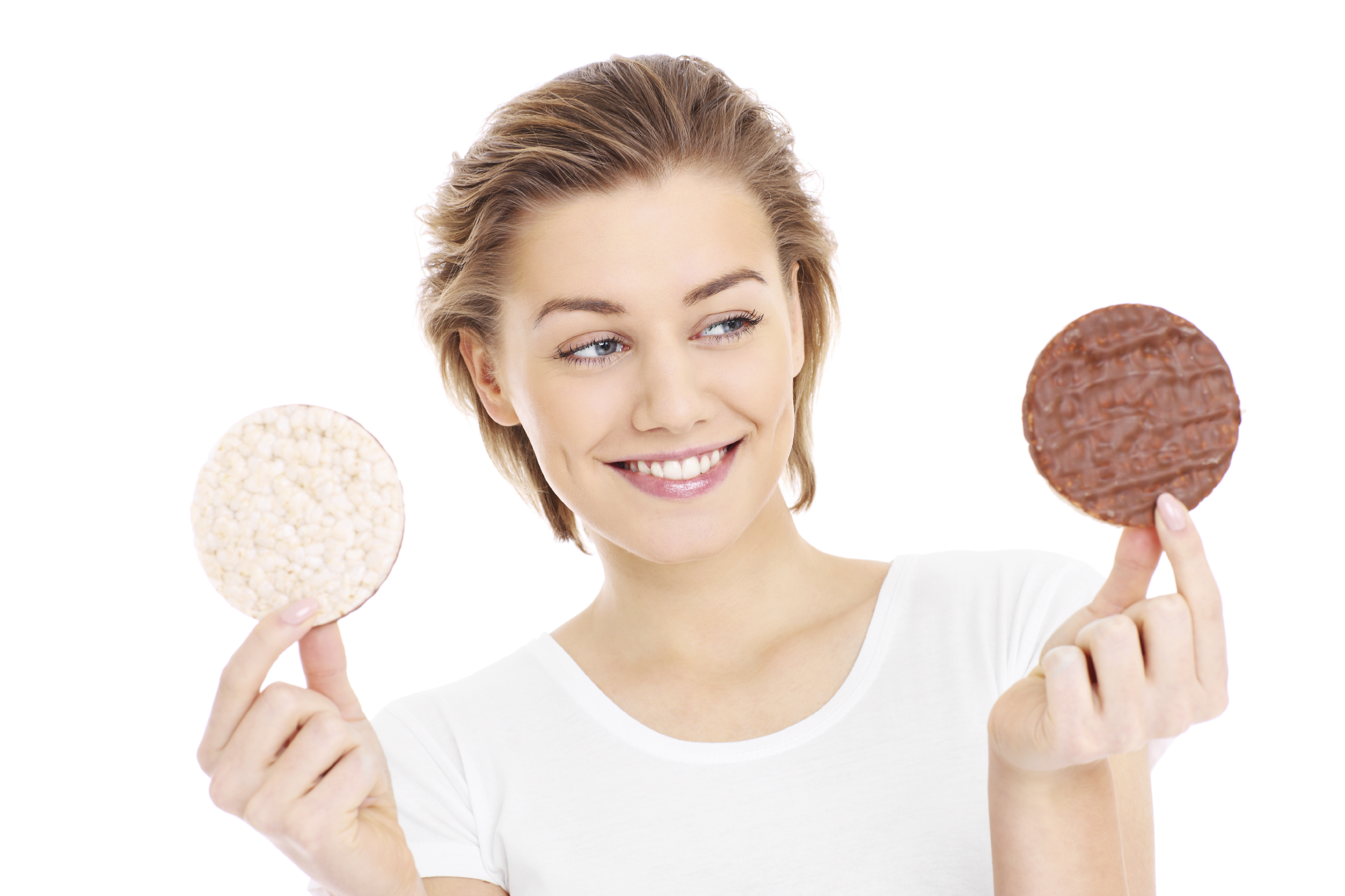 A portrait of a young pretty woman trying to decide between a healthy and unhealthy cookie over white background
